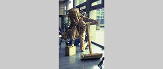 Title: Keverne Late for Work. Sited in the foyer of Leeds Polytechnic building. Wood sculpture 1981